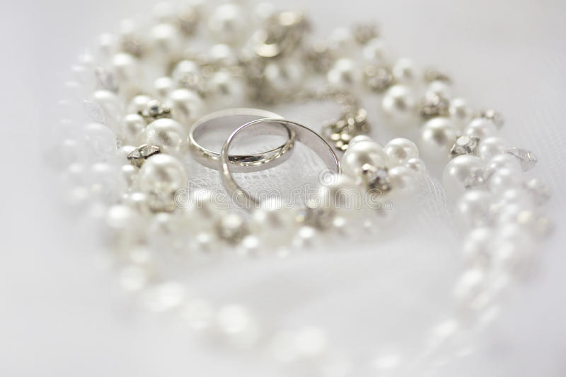 Zilveren bruiloftringen en parelhalsband royalty-vrije stock afbeeldingen