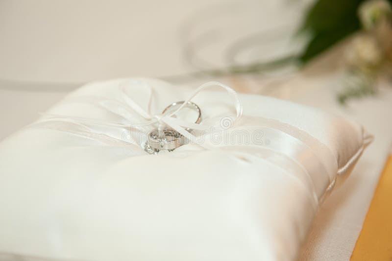 Zilveren bruiloftringen op een wit zijdehoofdkussen stock afbeelding