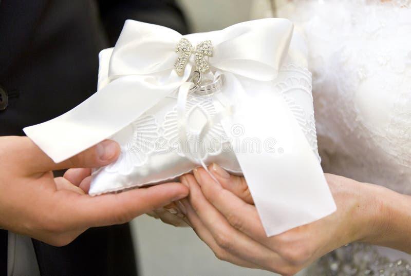 Zilveren bruiloftringen op wit decoratief hoofdkussen stock foto's