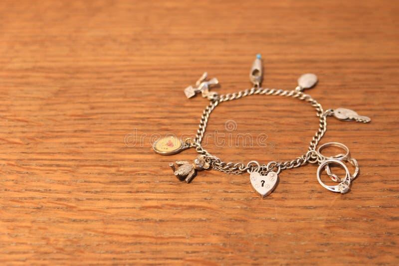 Zilveren charmearmband op een gekraste houten achtergrond royalty-vrije stock afbeeldingen