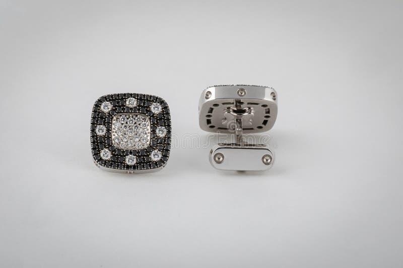 Zilveren cufflinks met zwarte diamanten en witte die diamanten in het midden, op witte achtergrond wordt geïsoleerd royalty-vrije stock afbeeldingen