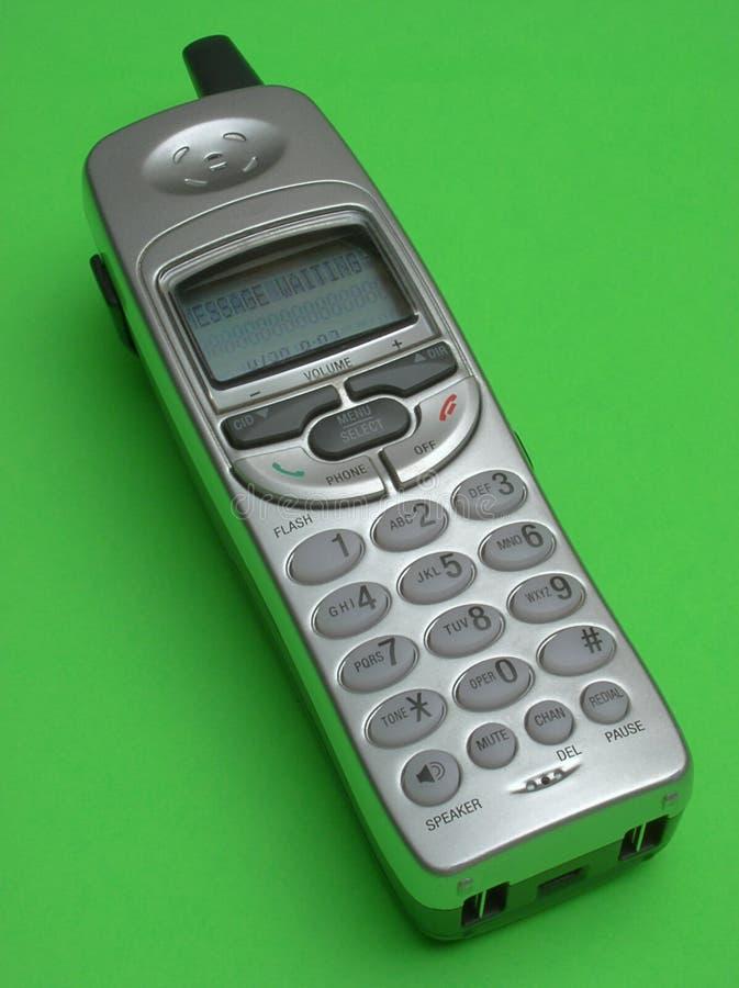 Zilveren draadloze telefoon op groene achtergrond royalty-vrije stock fotografie