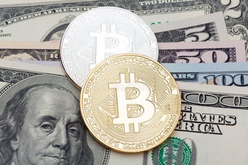 Zilveren en gouden bitcoin op Amerikaanse dollarbankbiljetten stock afbeeldingen