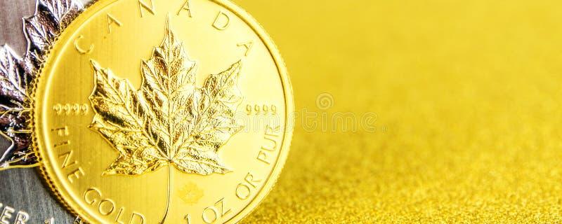 Zilveren en gouden Canadees esdoornblad één onsmuntstukken op gouden achtergrond stock foto's