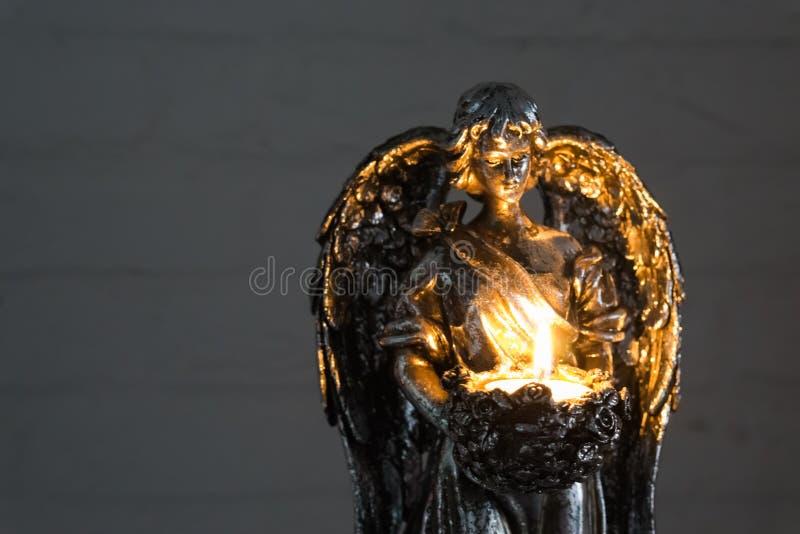 Zilveren engelenstandbeeld die een brandende kaars in close-up, Kerstmis en geestelijke traditie houden stock foto's
