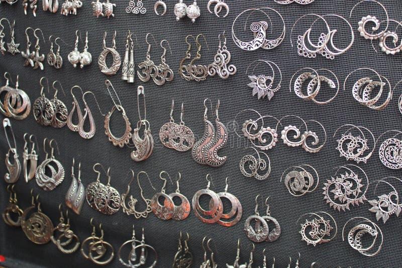 Zilveren gemaakte oorringenhand - royalty-vrije stock afbeeldingen