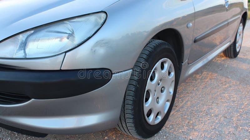 Zilveren grijze auto met kleine deuk en krassen aan kant Kar met schade van neerstortingsongeval, parkeerterrein of verkeer stock foto