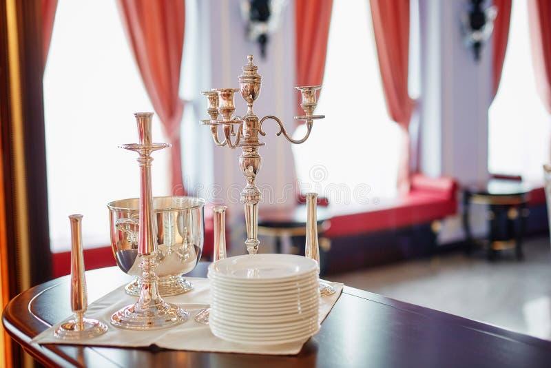 Zilveren kandelaars en een emmer voor het koelen van champagne Het exclusieve restaurant dienen stock foto