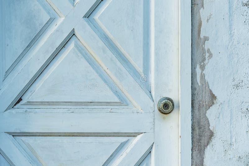 Zilveren knop op oude witte houten deur met concrete muur stock afbeelding