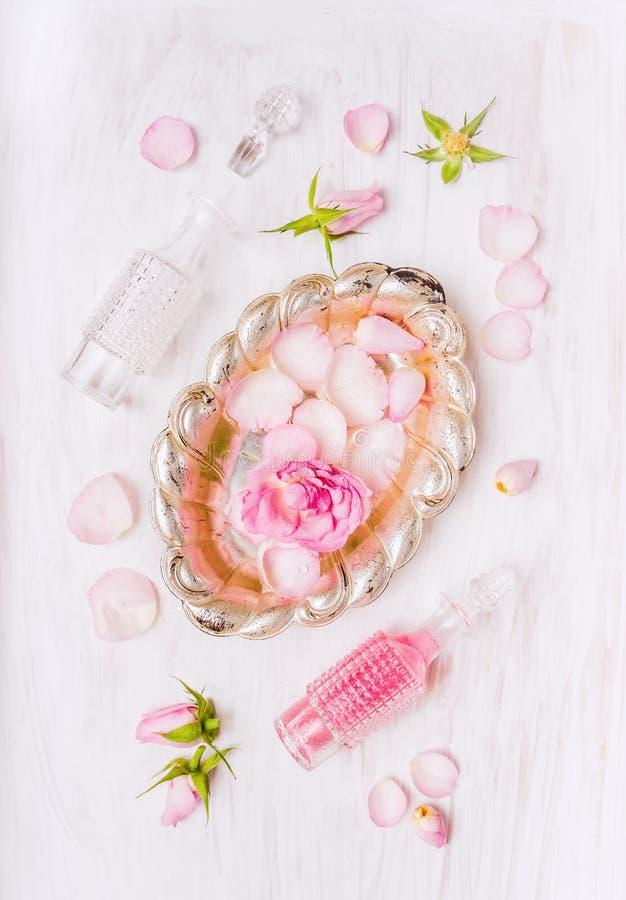 Zilveren kom met rozen in water, fles en knoppen en bloemblaadjes van rozen op witte houten royalty-vrije stock fotografie