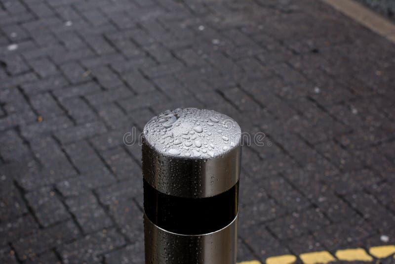 Zilveren Meerpaal in de regen aan het eind van een straat stock fotografie