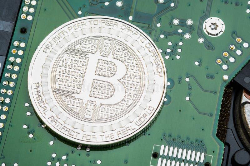 Zilveren metaalbitcoins op elektronische kringsmotherboard crypt stock fotografie