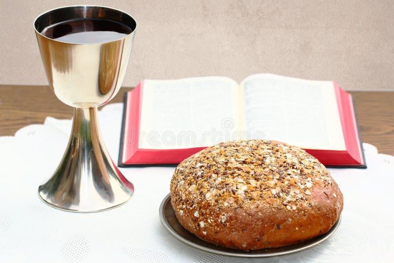 Zilveren miskelk, open Bijbel en brood stock afbeeldingen