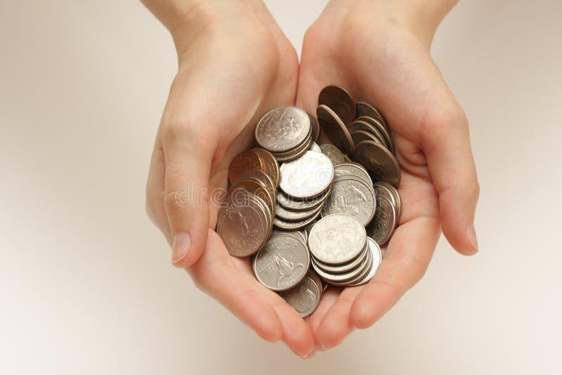 Zilveren muntstukken in handen stock afbeelding