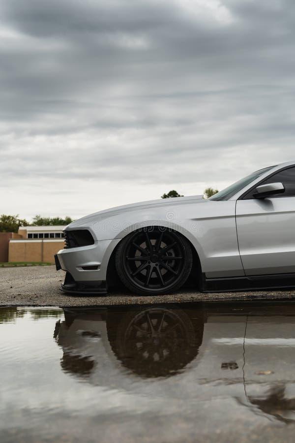 Zilveren Mustang onder Stormachtige Hemel met Bezinning royalty-vrije stock afbeelding