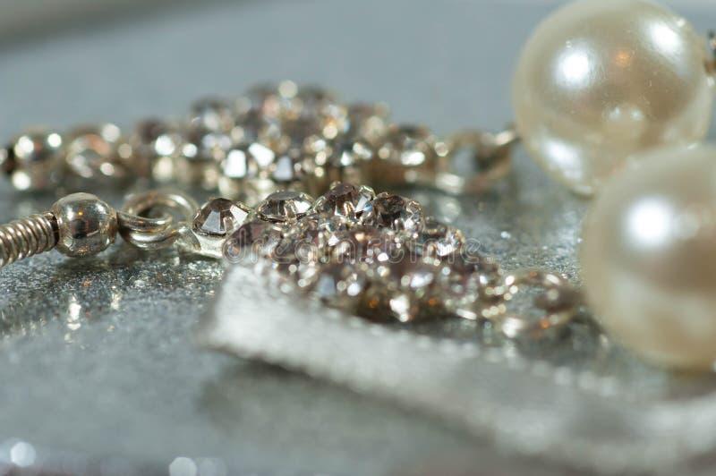 Zilveren oorringen met gemmen en parels op glanzende giftdoos stock afbeelding