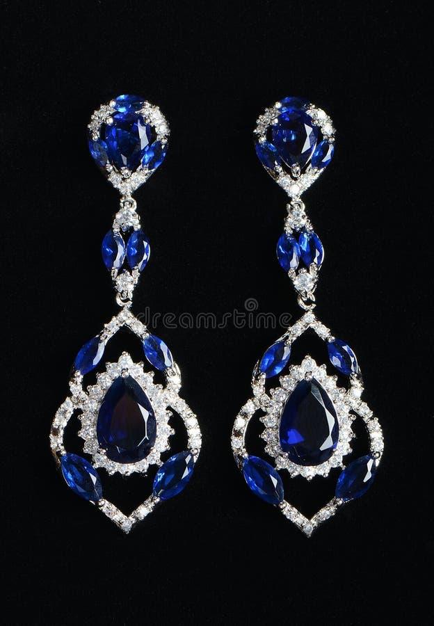 Zilveren oorringen met juwelen stock afbeeldingen