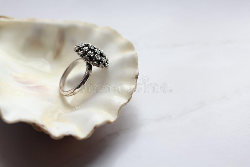 Zilveren ring met edelstenen op shell, marmeren achtergrond royalty-vrije stock afbeelding