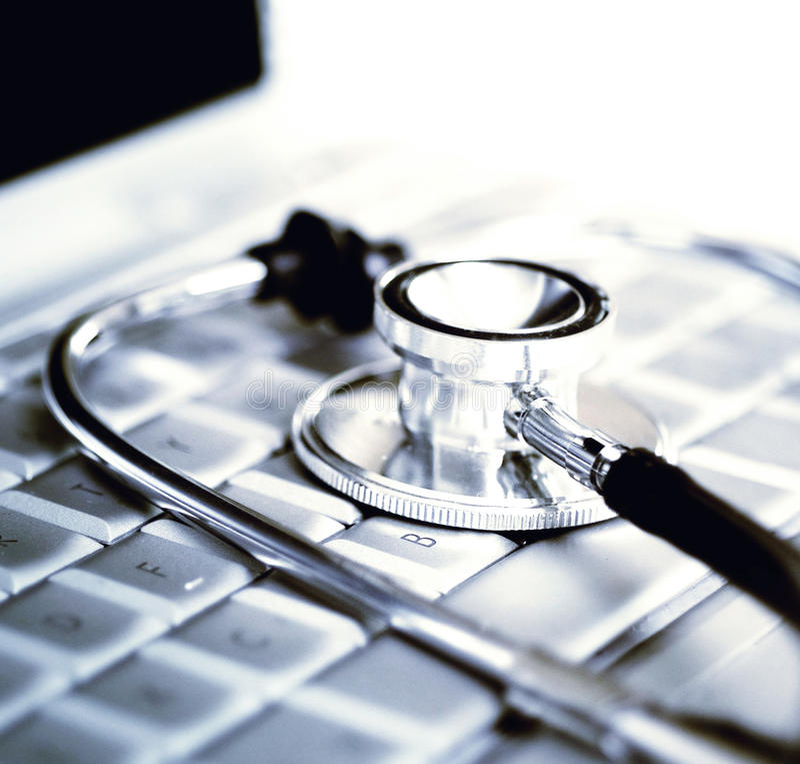 Zilveren stethoscoop over laptop toetsenbord stock afbeeldingen