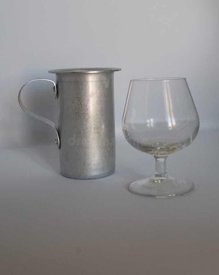 ZILVEREN waterkruik met cognacglas leeg op witte achtergrond stock fotografie