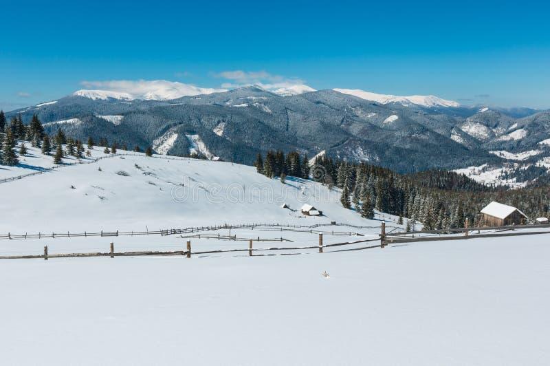 Zim śnieżne góry i samotny domostwo, obraz stock
