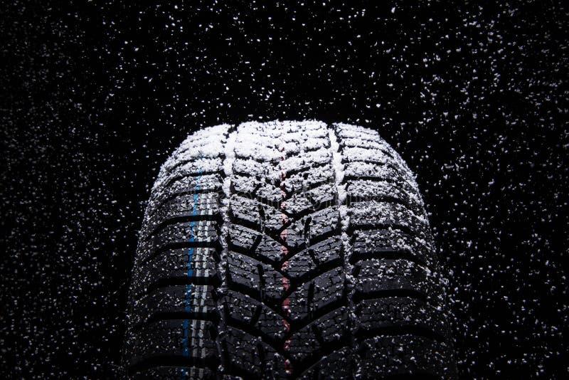 Zim Samochodowe opony z śnieżnymi płatkami na czarnym tle zdjęcie stock