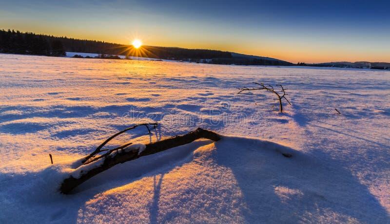 Zima śnieżny krajobraz zaświecał położenia słońcem fotografia stock