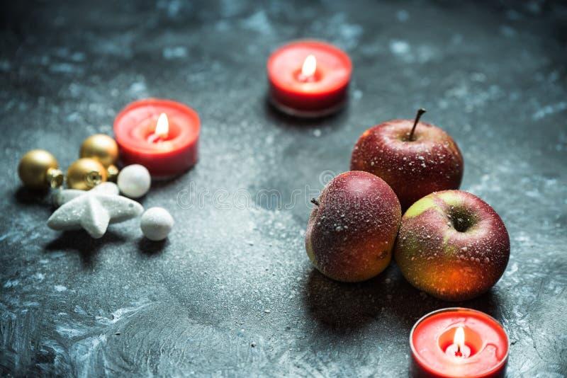 Zima czas, zimy czerwony jabłko i świeczki w śniegu, zdjęcie stock