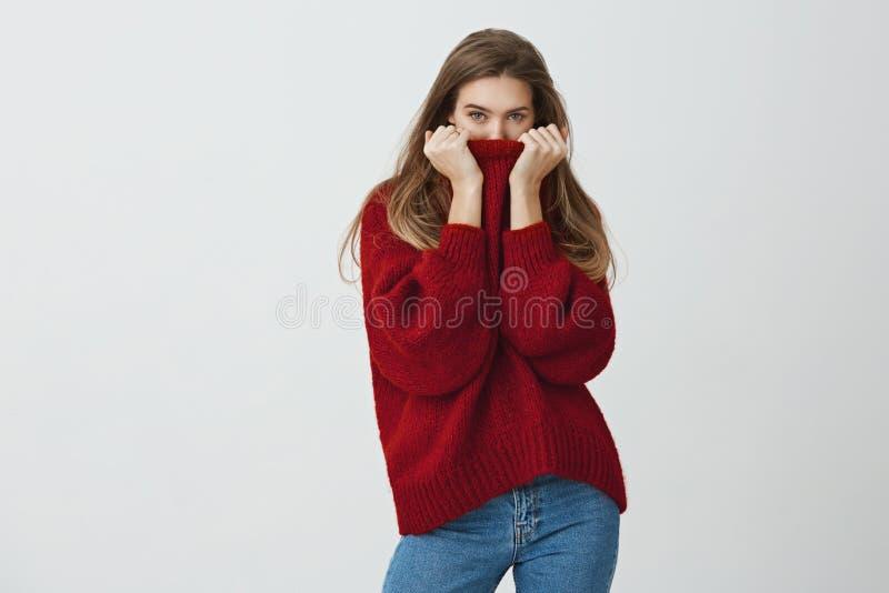 Zima jest zamknięta Atrakcyjna nikła kobieta w modnym luźnym pulowerze chuje twarz w kołnierzu podczas gdy spoglądający przy kame obraz royalty free