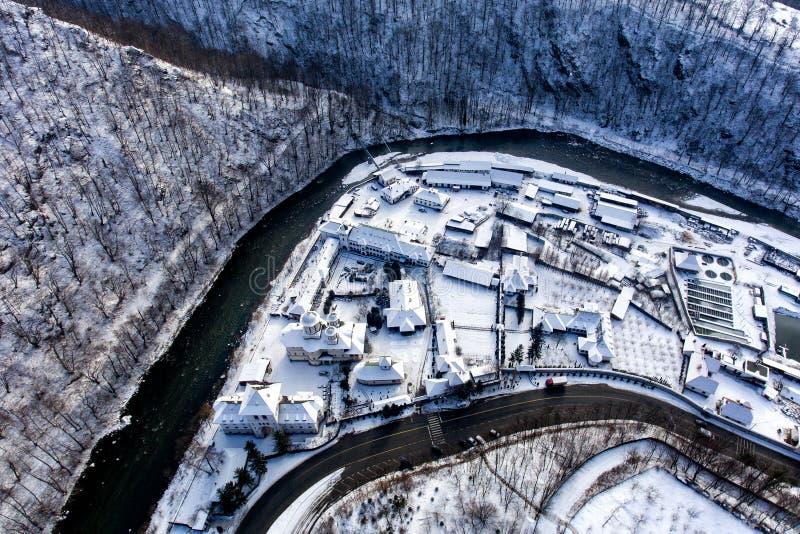 Zima krajobraz wzdłuż rzecznej doliny w Rumunia z widokiem Lainici monasteru od above obrazy stock