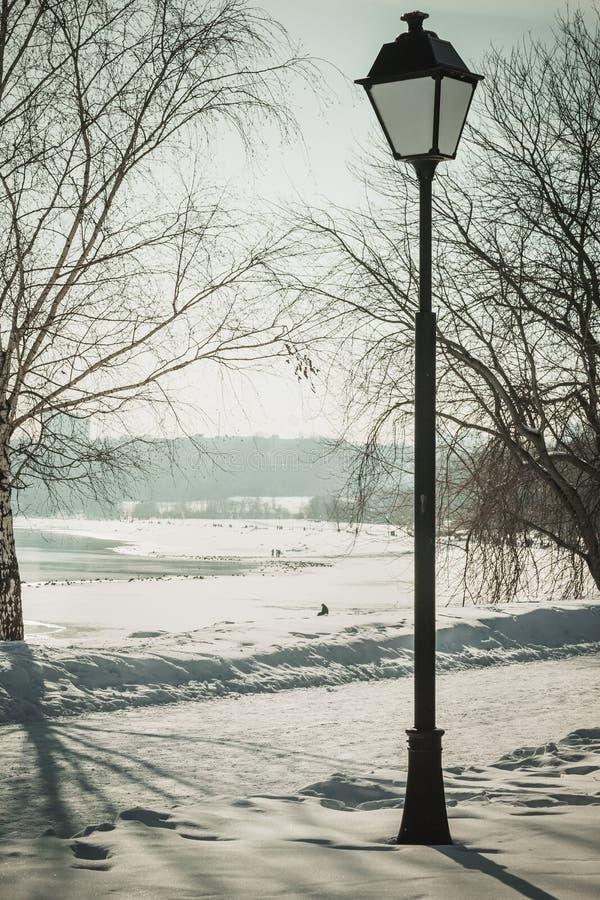 Zima krajobraz z parkowym lampionem i zamarzniętą rzeką, rocznik zdjęcia stock