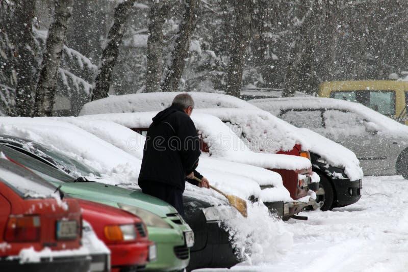Zima Mężczyzna z miotłą czyści samochód od śniegu na ulicie po dużego śnieżycy w mieście, wszystkie samochody pod śniegiem, lodow obraz royalty free