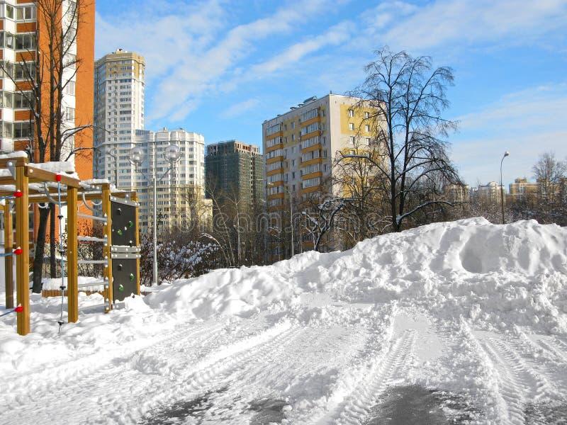 Zima miastowy krajobraz, domy, wielki snowdrift na sportach gruntuje, jasny dzień zdjęcia stock