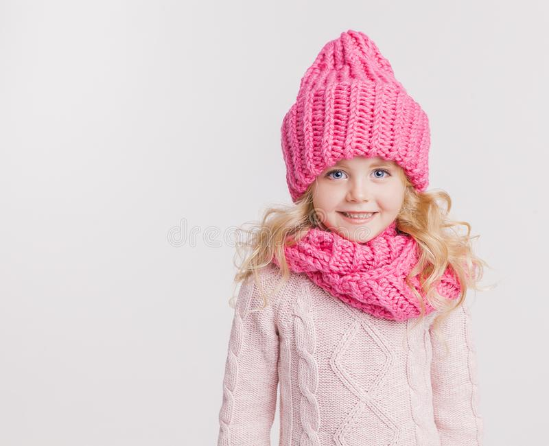 Zima odziewa Portret mała kędzierzawa dziewczyna w trykotowym różowym zima kapeluszu, szaliku i fotografia stock