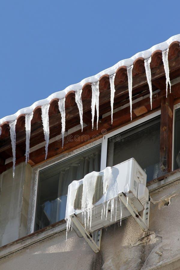 Zima Ogromni niebezpieczni lodowi sople wieszają nad zagrożeń zdrowie uliczny życie ludzie wiesza od dachu budynek i obrazy royalty free