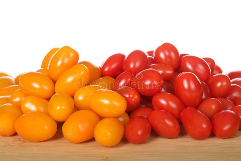 Zima, an orange grape tomatoes next to Angel Sweet grape Tomatoes stock photos