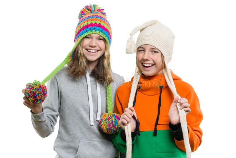 Zima portret dwa szczęśliwej one uśmiechają się ładnej dziewczyny w trykotowych kapeluszach ma zabawę, odizolowywający na tle, lu zdjęcie royalty free