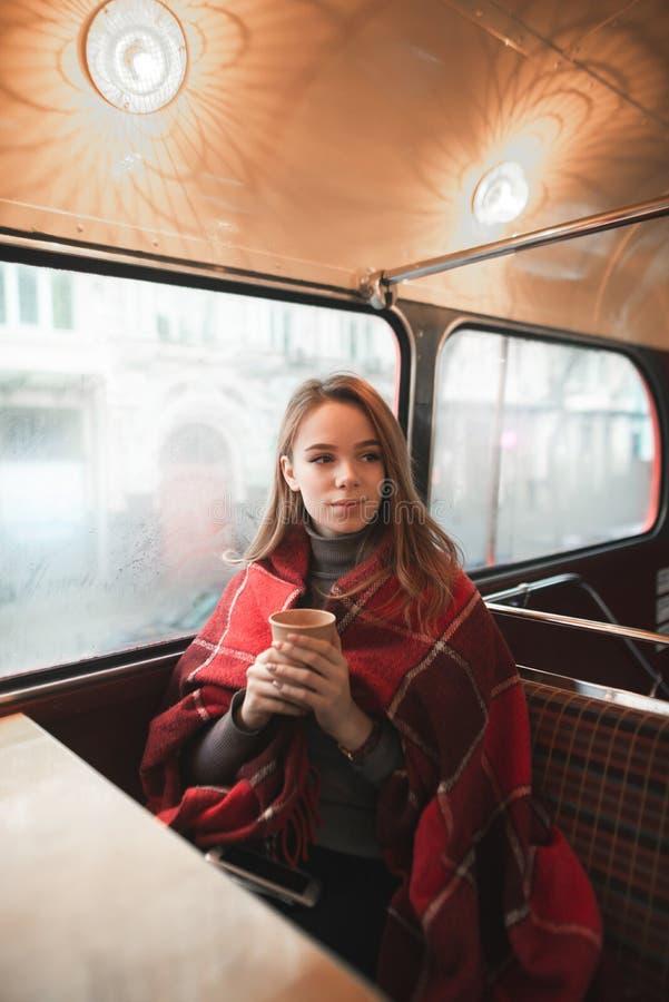 Zima portret młoda dziewczyna, zakrywający z koc, siedzi z filiżanka kawy i spojrzeniami blisko okno strona zdjęcie stock