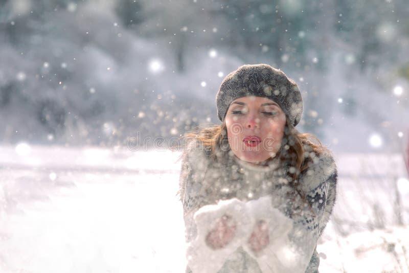 Zima portret Potomstwa, pięknej kobiety podmuchowy śnieg w kierunku kamery na zimy tle zdjęcie royalty free