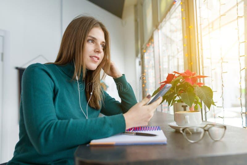Zima portret studencki dziewczyny studiowanie w cukiernianym obsiadaniu z filiżanka kawy Młodej kobiety studiowanie używać smartp obraz stock