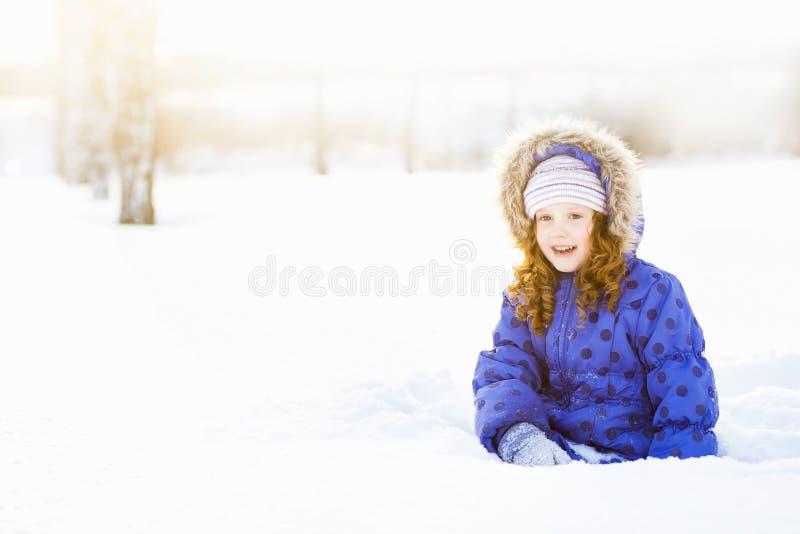 Zima portret uśmiechnięta dziewczyna, siedzi w śniegu pa zdjęcia royalty free