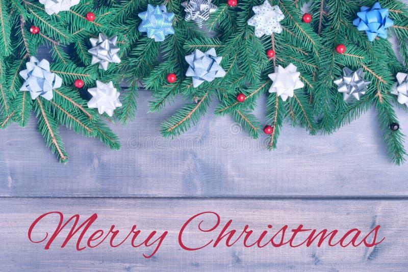 Zima skład z wpisowymi Wesoło bożymi narodzeniami Gałąź choinka pięknie rozkładają na drewnianym fotografia stock