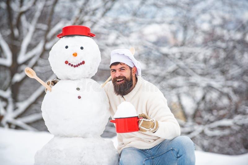 Zima szefa kuchni kucharz Brodaty szef kuchni z bałwanu kucharzem przy słonecznym dniem w zima parku Śmieszna zimy kartka z pozdr zdjęcie stock