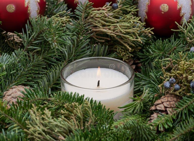 Zima wakacje dekoracja: fraser jodły stołu wianku centerpiece z rożkami, jałowem, choinek piłkami i płonącą świeczką, fotografia stock