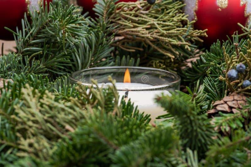 Zima wakacje dekoracja: fraser jodły stołu wianku centerpiece z rożkami, jałowem, choinek piłkami i płonącą świeczką, zdjęcie stock