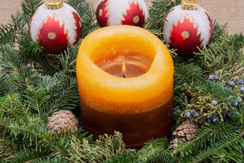 Zima wakacje dekoracja: fraser jodły stołu wianku centerpiece z rożkami, jałowem, choinek piłkami i płonącą świeczką, obraz stock