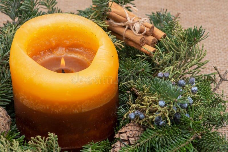 Zima wakacje dekoracja: fraser jodły stołu wianku centerpiece z rożkami, jałowem, płonącą świeczką i cynamonowymi kijami, fotografia royalty free