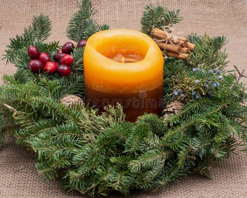 Zima wakacje dekoracja: fraser jodły stołu wianku centerpiece z rożkami, jałowiec, płonąca świeczka, cynamonowi kije fotografia royalty free