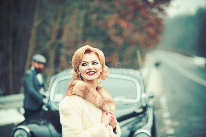 Zima wakacji wycieczka samochodowa na wakacje i podróży ludzie pojęć - uśmiechnięci młodzi przyjaciele nad retro samochodem obraz stock