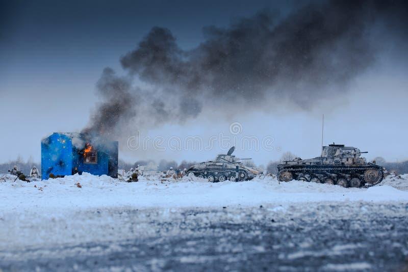 Zima widok niemieccy zbiorników panzers w ataku z palenie domem obrazy royalty free